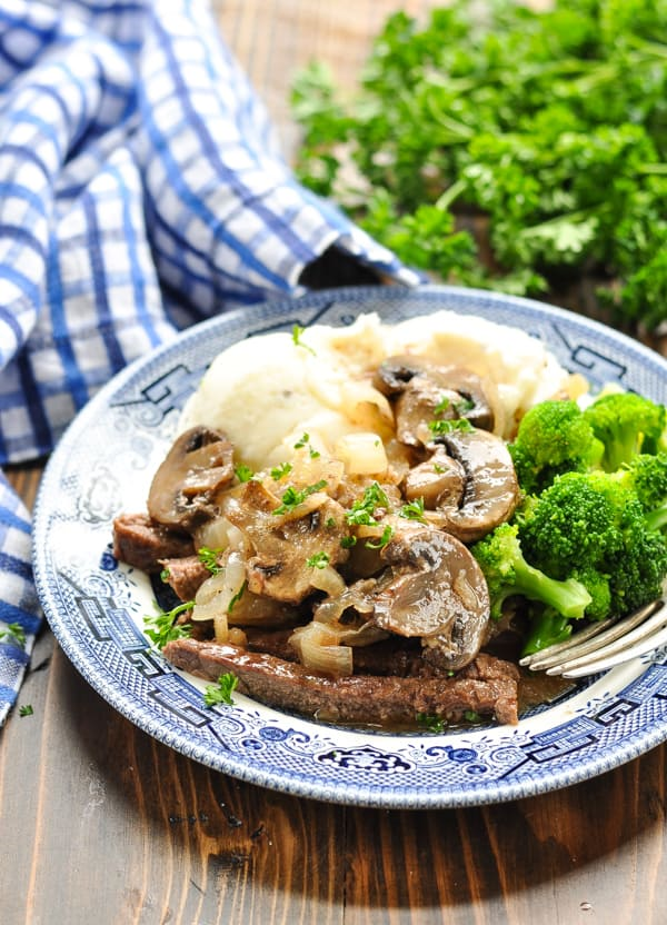 Close up shot of round steak on blue and white plate served with mashed potatoes