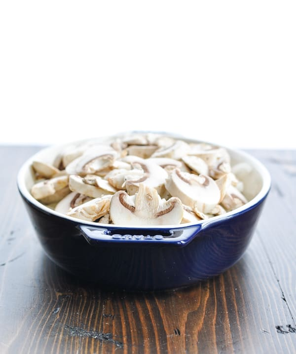 Sliced mushrooms and onions in blue baking dish over steak