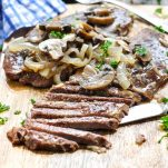 Sliced top round steak topped with mushrooms and onions on a cutting board
