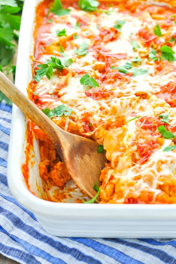 A close up of a stuffed cabbage casserole in a white dish with a wooden spoon