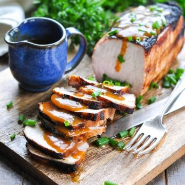 Sliced marinated grilled pork loin on a cutting board