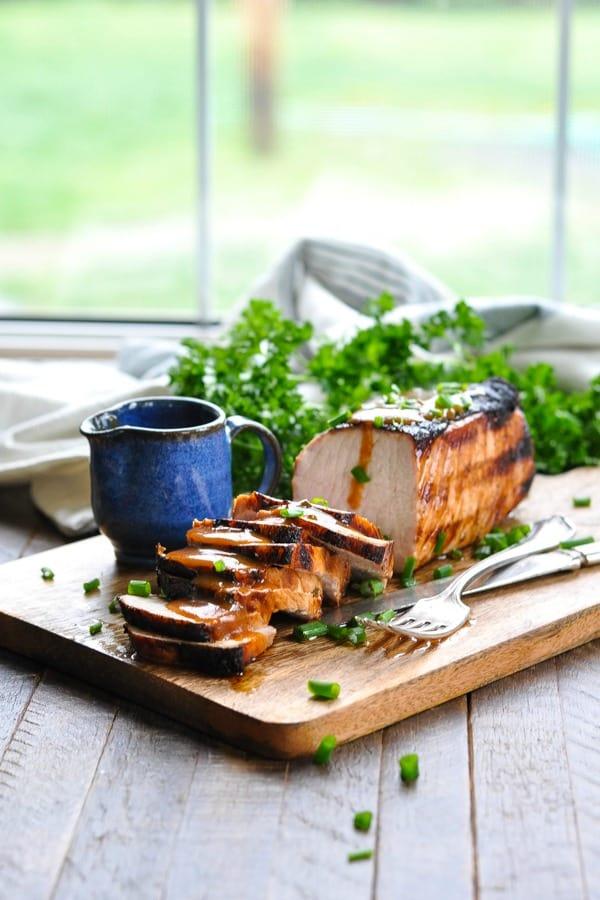 Grilled pork loin filet sliced on a cutting board