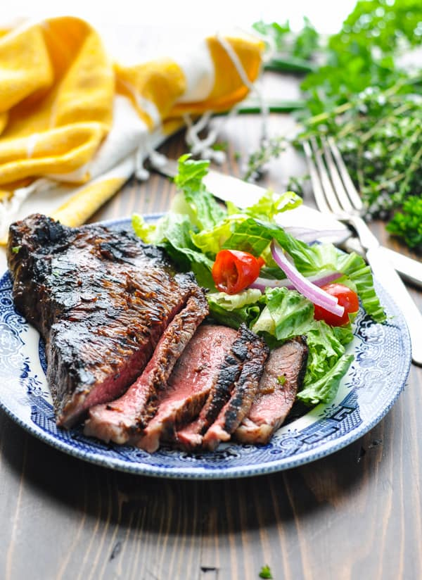 Sliced marinated grilled steak on a plate with salad
