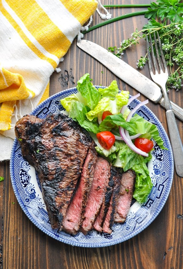 Overhead shot of grilled New York Strip steak on a plate with salad