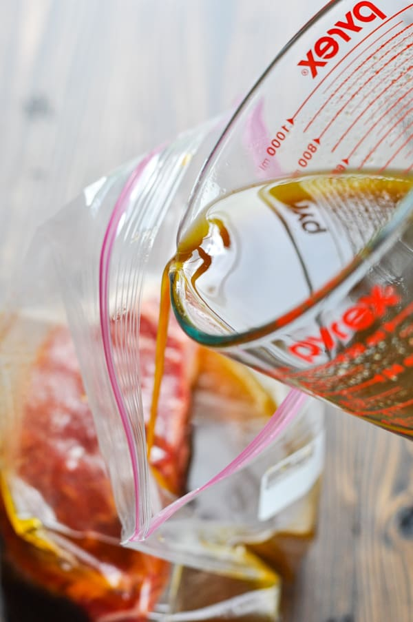 Pouring marinade over steak in a ziploc bag