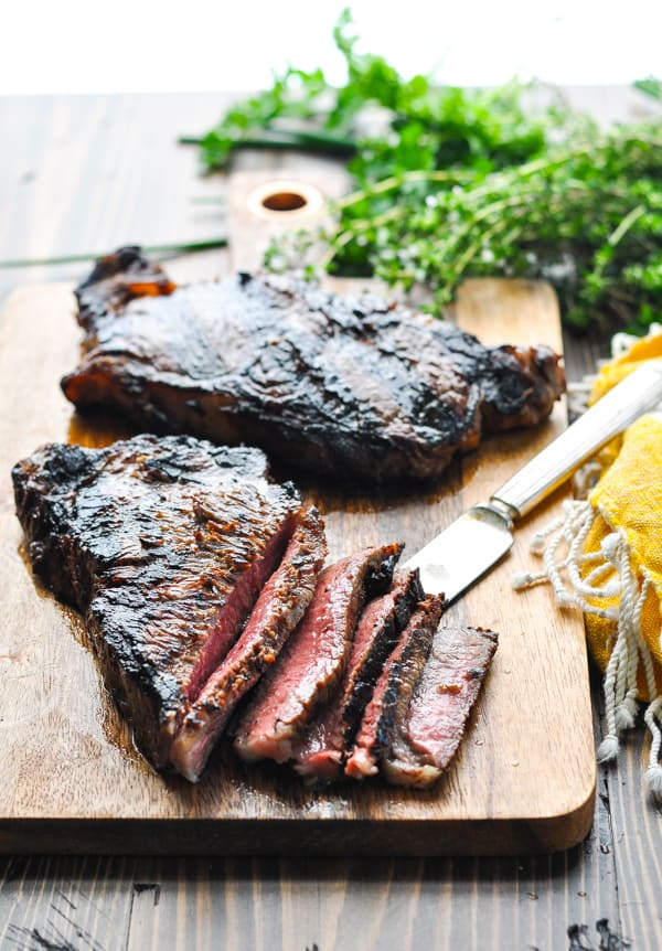 Sliced marinated grilled steak on a cutting board