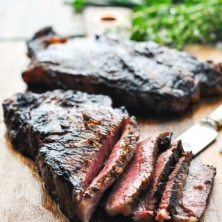 Sliced New York Strip Steaks on a cutting board after using a steak marinade and grilling