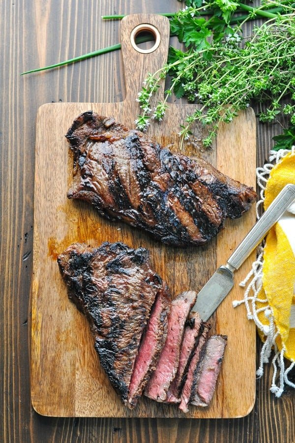 Overhead shot of the best steak marinade on grilled New York Strip Steaks on a cutting board