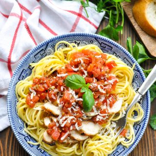 Overhead shot of bowl of Tomato Pesto Pasta with Grilled Chicken surrounded by fresh herbs