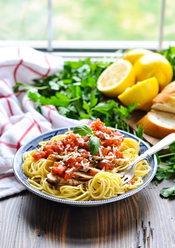 Fork twirling pasta with tomato pesto sauce and grilled chicken in a bowl