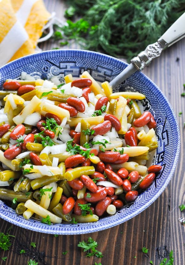 Close up shot of three bean salad in a blue and white serving bowl garnished with parsley