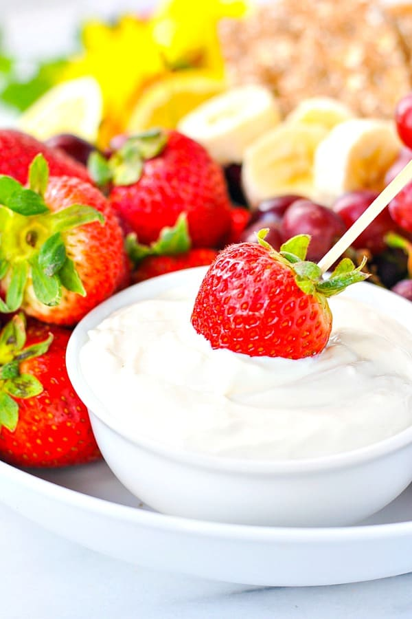 Dipping a strawberry into a fresh fruit dip