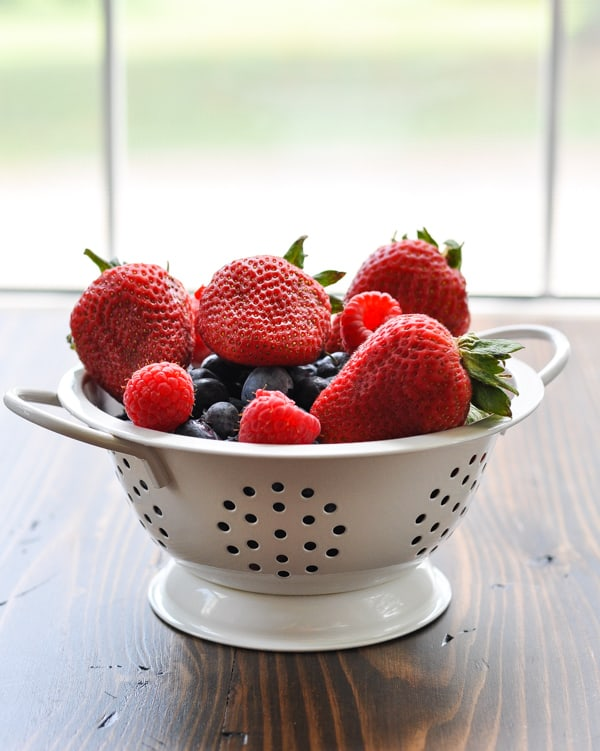 Fresh berries in a white colander