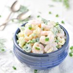 Front shot of Aunt Bee's Shrimp and Pasta Salad in a blue serving bowl garnished with sliced green onions