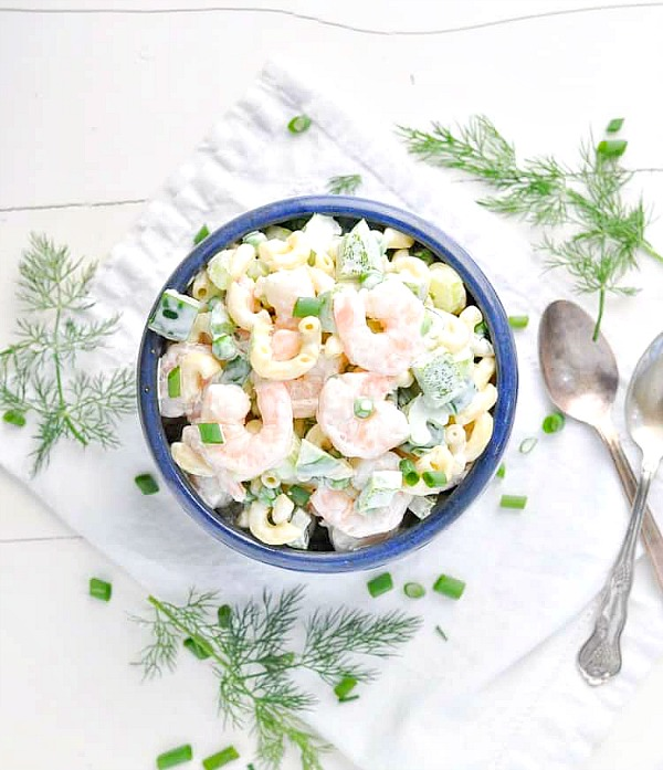 Pasta salad with shrimp in a blue bowl surrounded by fresh herbs