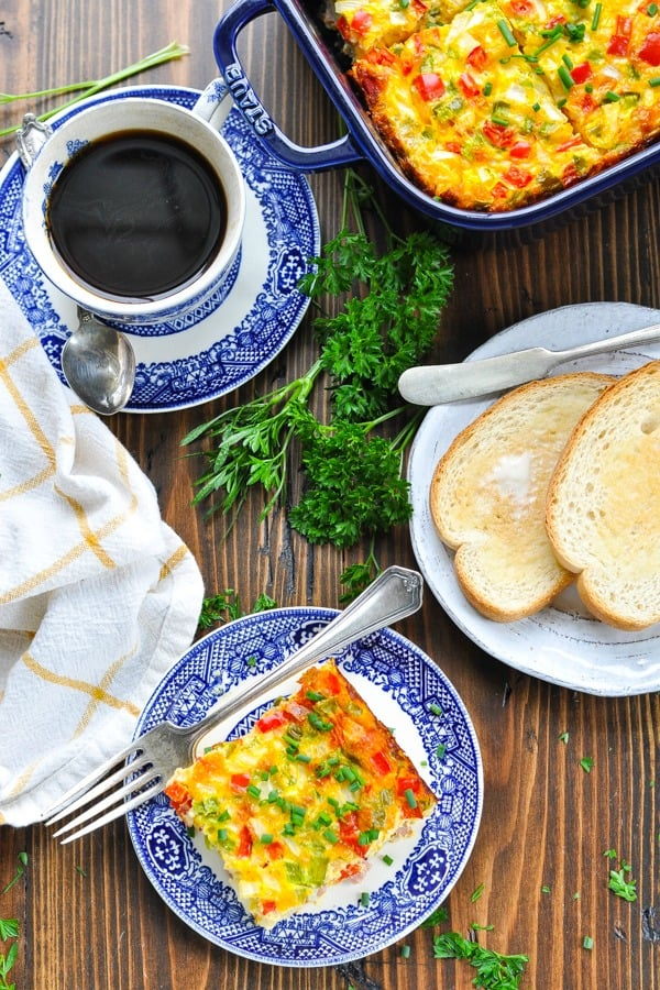 Long overhead shot of baked Denver omelet on a plate with coffee and toast