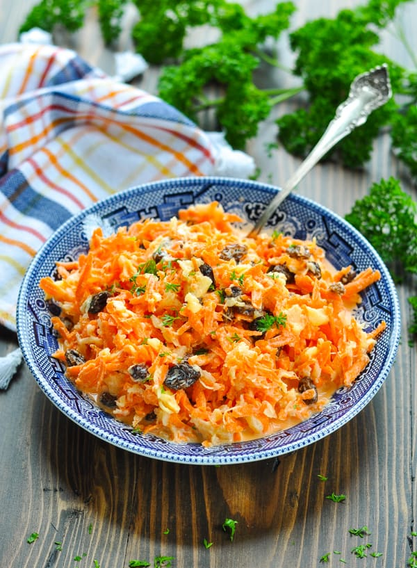 Carrot salad with pineapple and raisins in a blue and white serving bowl