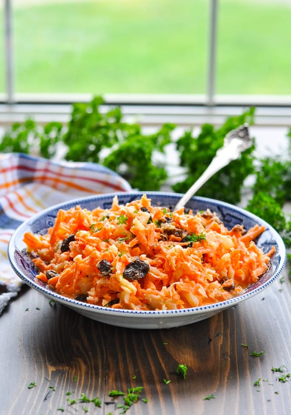 Front shot of carrot salad in a blue and white serving bowl