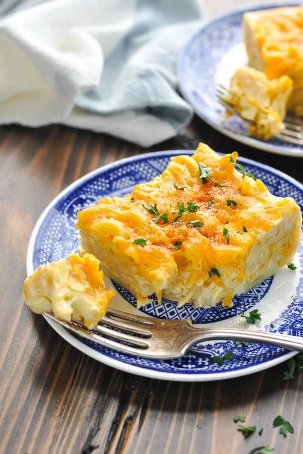 Piece of crock pot mac and cheese on a blue and white plate with a bite on a fork