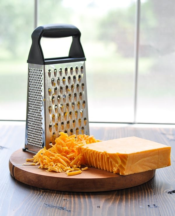 Grating block of cheddar cheese on a cutting board