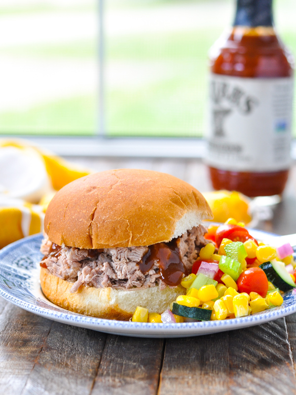 Crock Pot pulled pork sandwich on a plate with salad