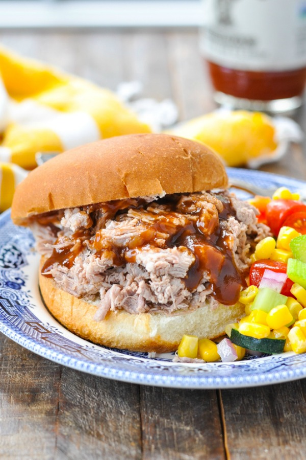 Pulled pork sandwich with barbecue sauce and corn salad on a blue and white plate