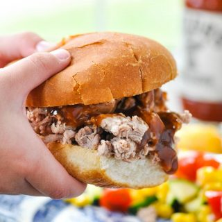 Kids hands holding a Crock Pot Pulled Pork Barbecue Sandwich