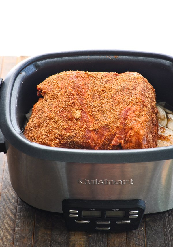 Pork shoulder with seasoning rub on it in Crock Pot