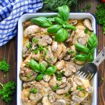 Long overhead shot of baked chicken and mushrooms garnished with fresh herbs