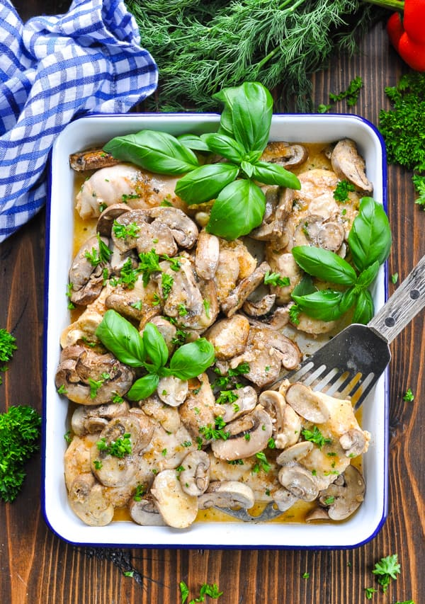Overhead shot of baked chicken breasts topped with mushrooms and fresh basil on a spatula