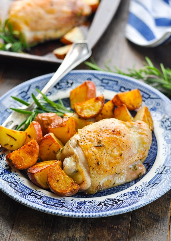 Baked chicken thigh with crispy potatoes on a blue and white plate