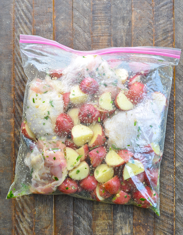 Potatoes and chicken thighs marinating in rosemary marinade in bag