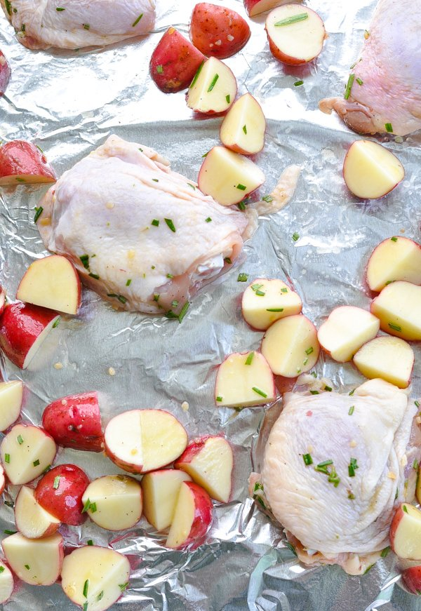 Raw chicken thighs and red potatoes on baking sheet before roasting