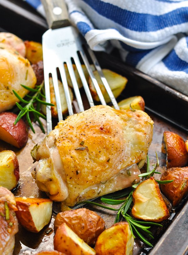 Rosemary chicken on a serving spatula surrounded by potatoes