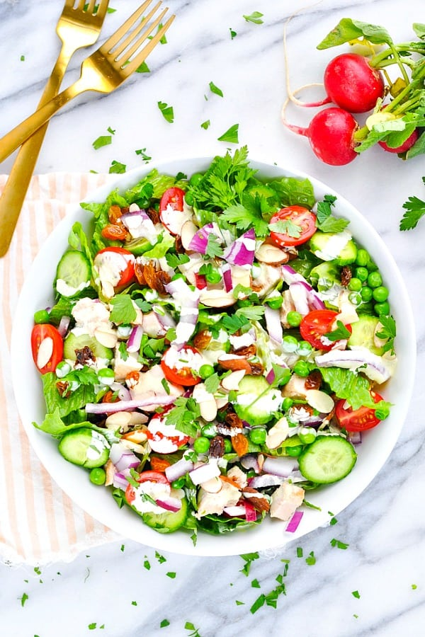 Overhead shot of curry chicken salad in a white bowl with vegetables and radishes
