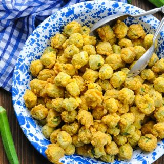 Close up overhead shot of crispy fried okra in a blue and white serving dish