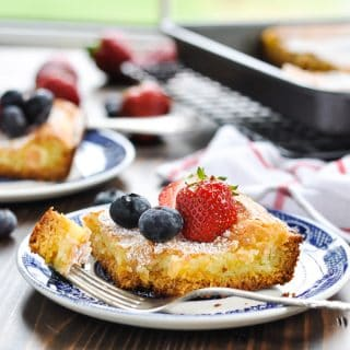 Slice of gooey butter cake with fresh berries on a plate with a bite on a fork