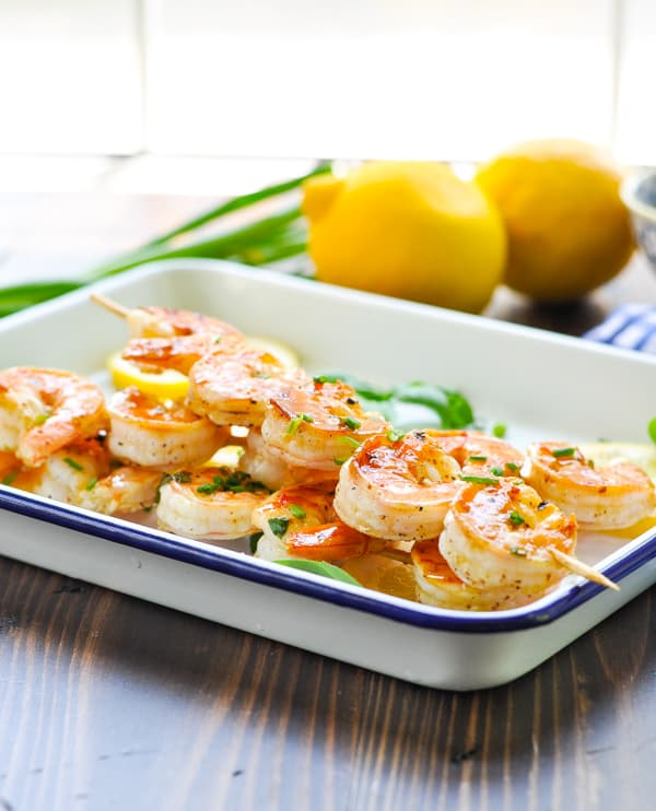 Side view of grilled shrimp skewers piled on a serving tray