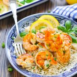 Piece of grilled shrimp on a fork in a bowl with rice