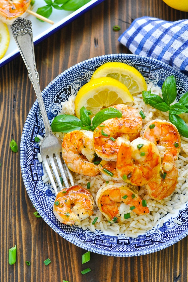Marinated grilled shrimp served over rice in a blue and white bowl