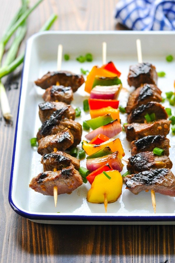 Front shot of easy marinated steak kabobs on a blue and white serving tray