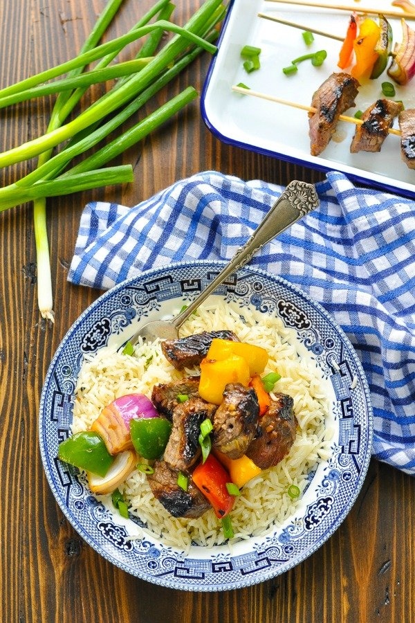 Overhead shot of grilled steak and vegetables in a bowl of rice