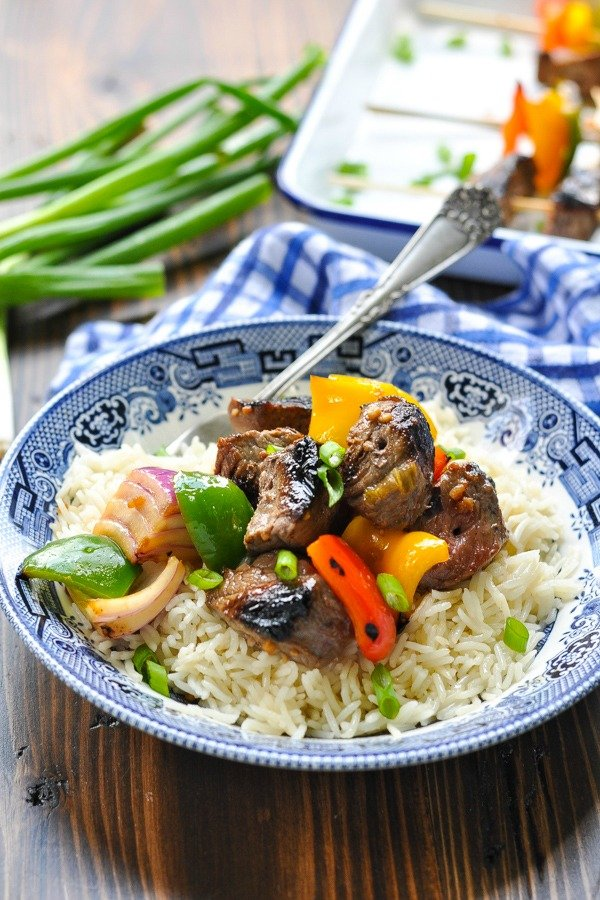 Front shot of bowl of beef kabobs and vegetables in a bowl with rice
