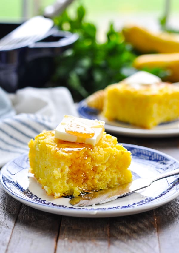 Slice of thick cornbread on a small plate topped with a pat of butter and a drizzle of honey