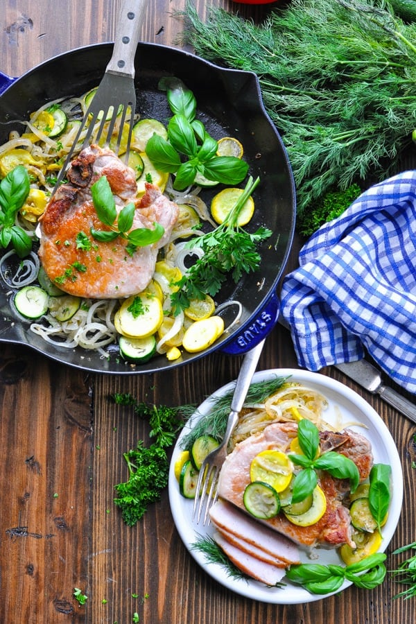 Long overhead shot of pork chops in a skillet and on a plate with fresh vegetables