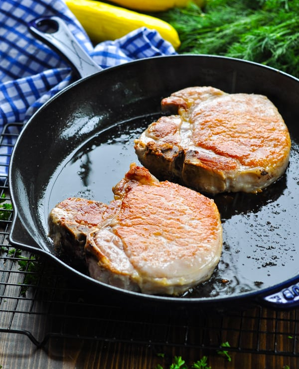 Two pork chops browned and fried in a cast iron skillet