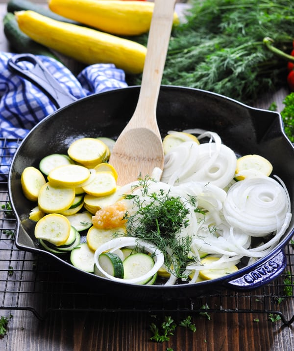 Zucchini squash onions and herbs in a cast iron skillet