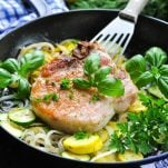 Pan fried pork chops in a skillet with zucchini and squash
