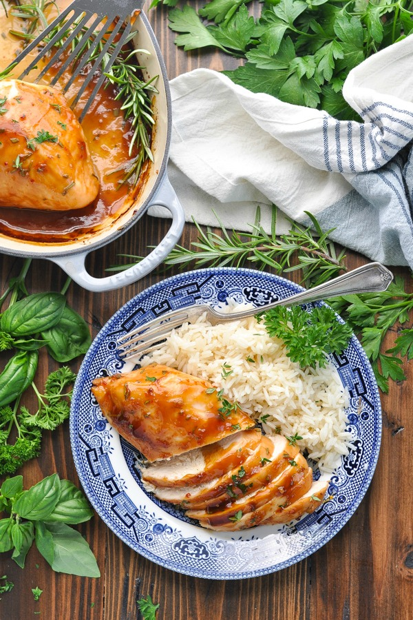Long overhead shot of a baked chicken breast on a plate with fork parsley and rice