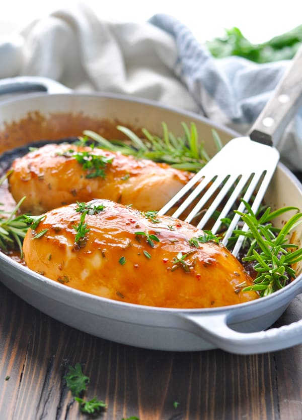 Baked chicken breast recipe in a baking dish with fresh rosemary